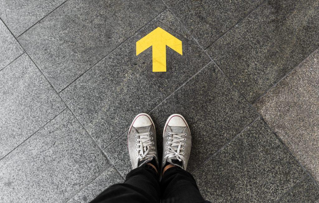 Uma seta no chão diante da pessoa ilustrando a necessidade de manter o foco em nossos objetivos