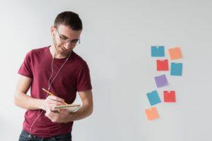 Jovem anotando ideias em seu caderno e post-it para realizar seu planejamento pessoal