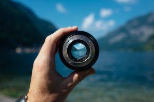 paradigma: pessoa segurando uma lente pela qual vê uma paisagem